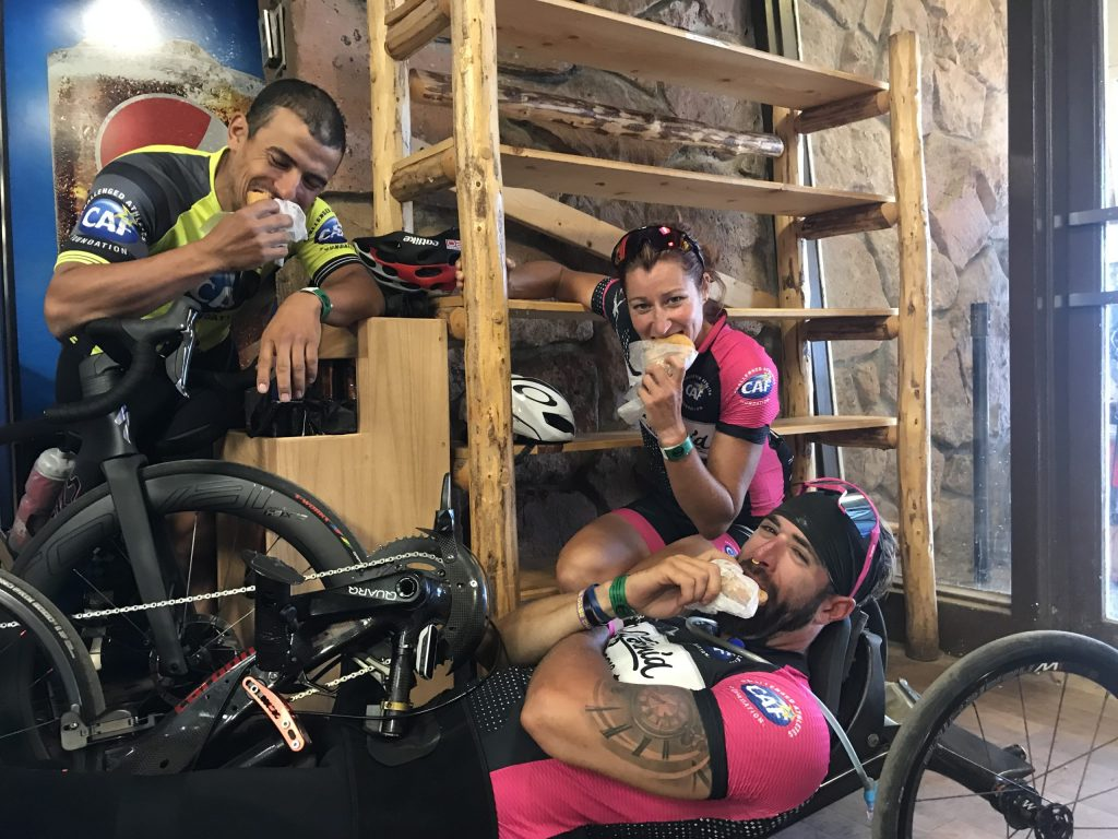 From top left: Mohamed Lahna, Jamie Whitmore, and Brandon Lyons eat sandwiches at the top of Pikes Peak after riding to the summit.