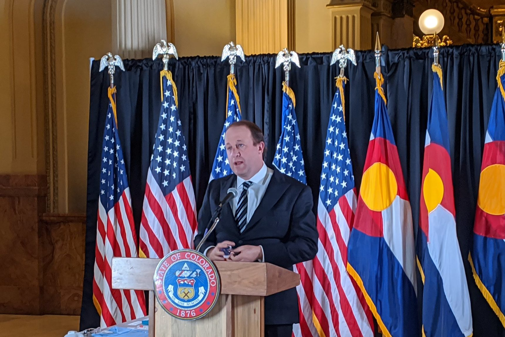 Gov. Jared Polis delivers an update on the Colorado response to the coronavirus from the west foyer of the state Capitol, April 29, 2020.