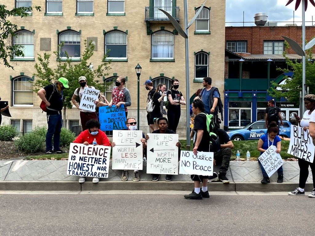 Demonstrators in the median along Nevada Ave. outside Colorado Springs City Hall on Sunday, May 31, 2020.