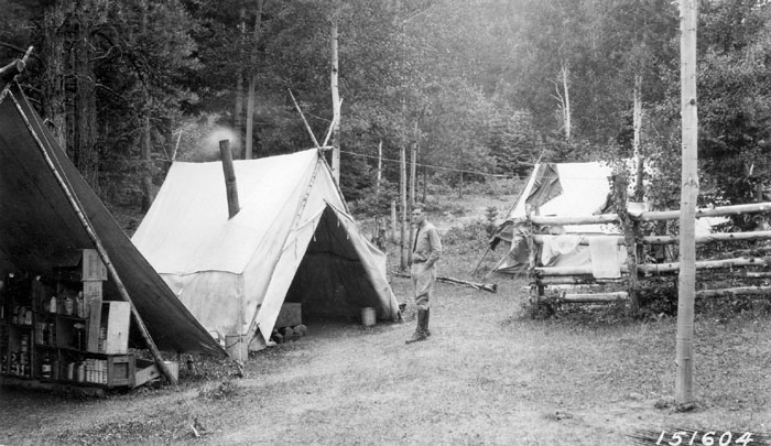 Arthur Carhart stands near the supply, cook and sleep tents at a construction camp in the San Isabel National Forest, Colorado near Beulah in July 1920.