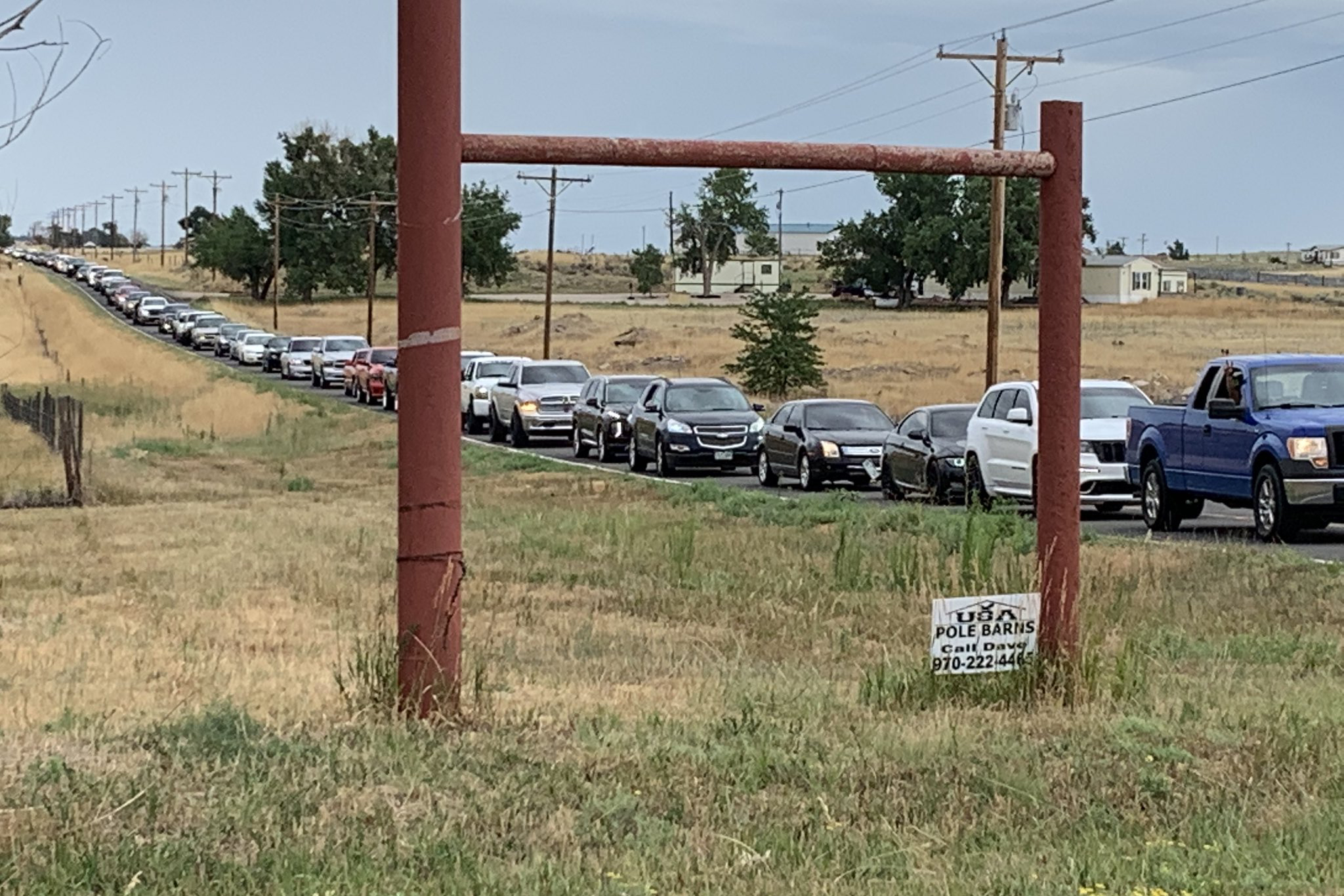Cars line up for a rodeo and concert event in Weld County that drew thousands before the landowner asked promoters to call it off.