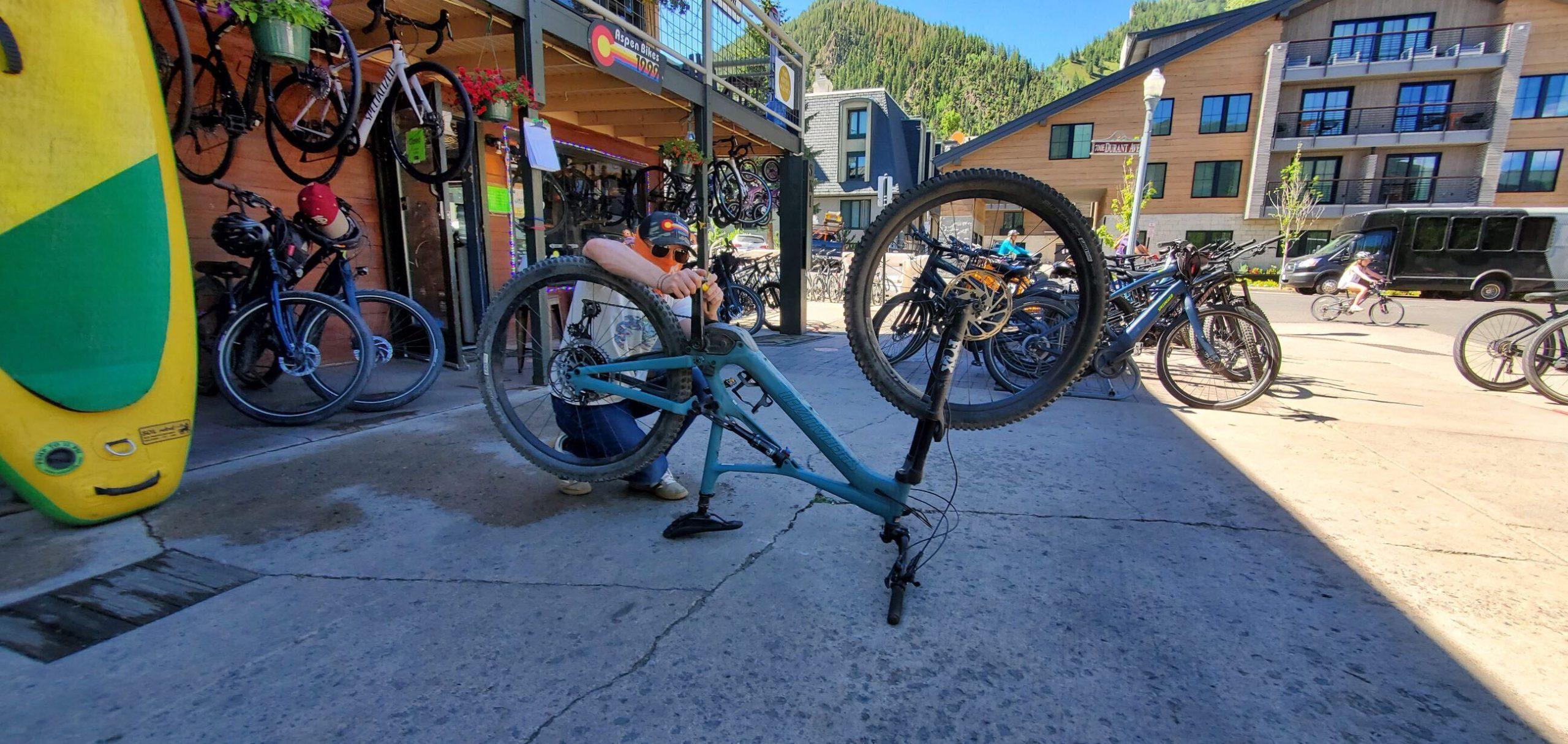 Blake Linehan puts pedals on a bike while working as a bike technician at Stapleton Ski/Aspen Bikes in Aspen, Colorado July 7, 2020.