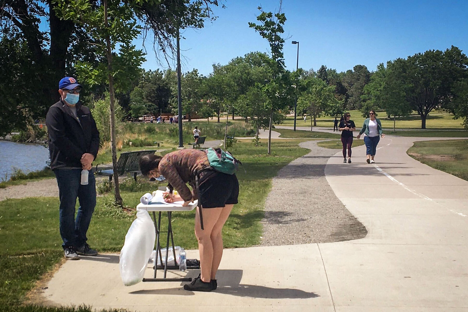 A petition circulator collects signatures at Denver's Sloan's Lake for a paid family leave measure that progressive groups hope to get on the ballot this November.