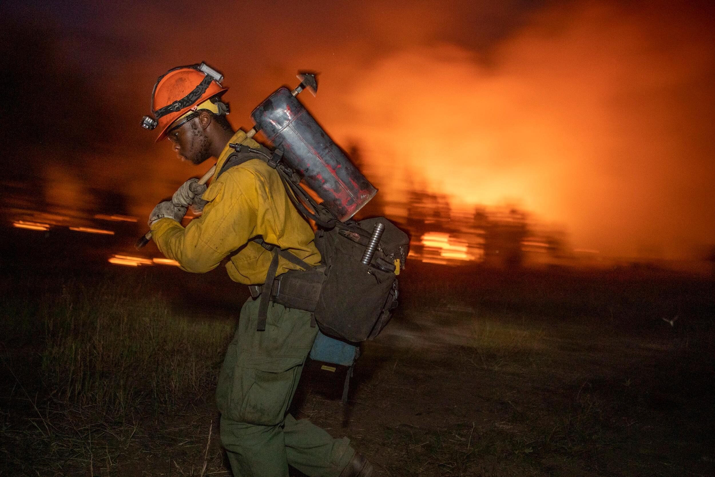 A Roosevelt Hotshot crew member carries fuel along the containment line as the burning operation progresses on the Williams Fork Fire. Aug. 24.