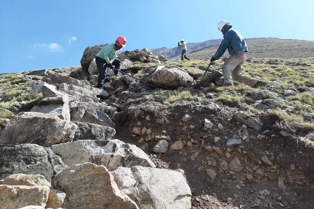 Volunteers work to move large boulders and rocks as they create a hiking trail on Colorado's Mt. Columbia near Buena Vista.