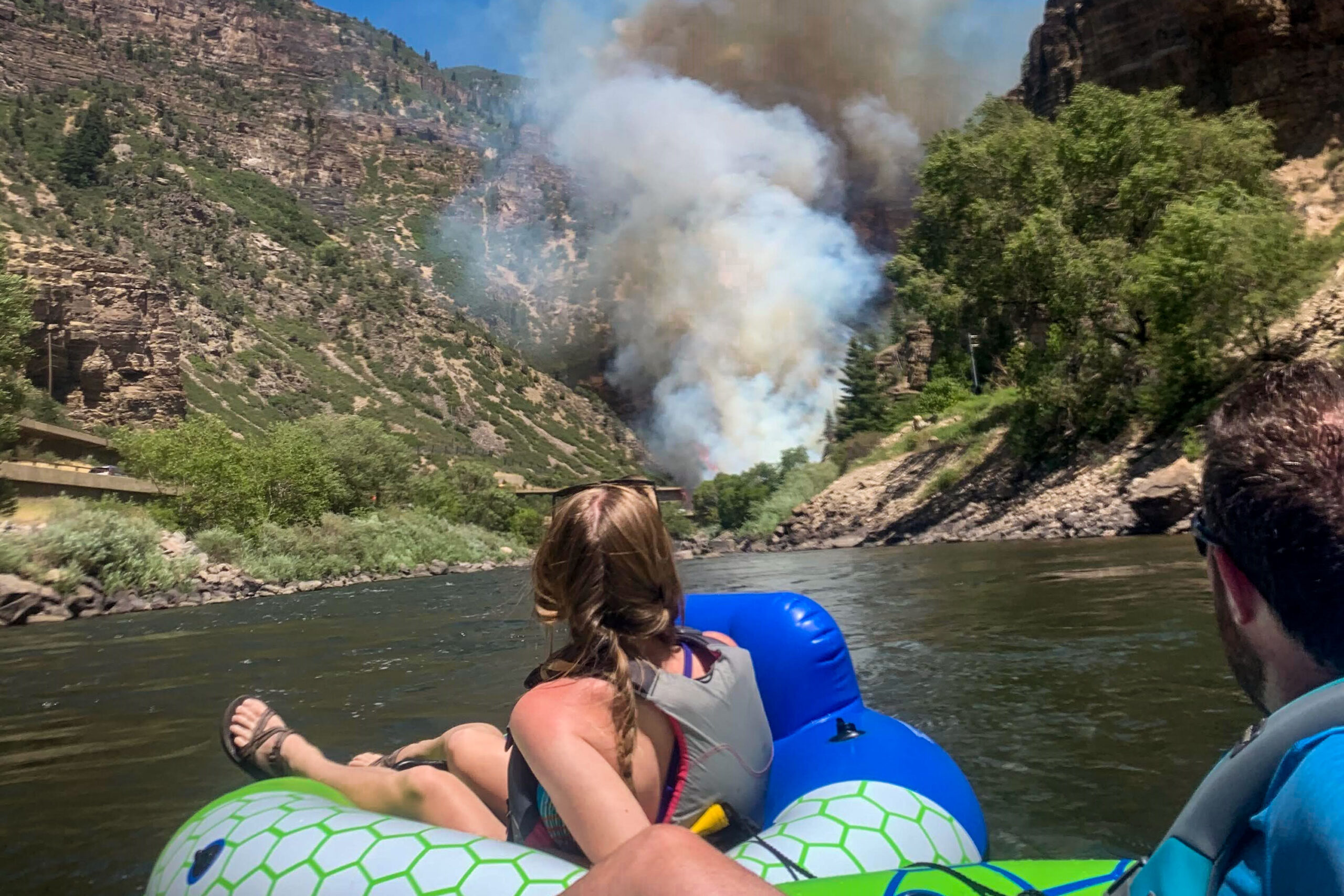 Lindsay Bobyak and Kyle Jones look on as smoke billows from fire along Interstate 70 in the Glenwood Canyon, Aug. 10, 2020.