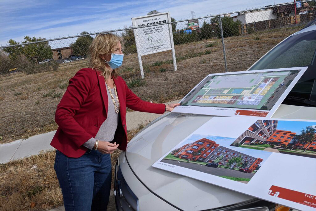 Homeward Pikes Peak Executive Director Beth Hall Roalstad, parked Oct. 16, 2020, alongside the empty lot where she is planning to build apartments for people who have experienced homelessness,  looking over renderings of the planned complex.