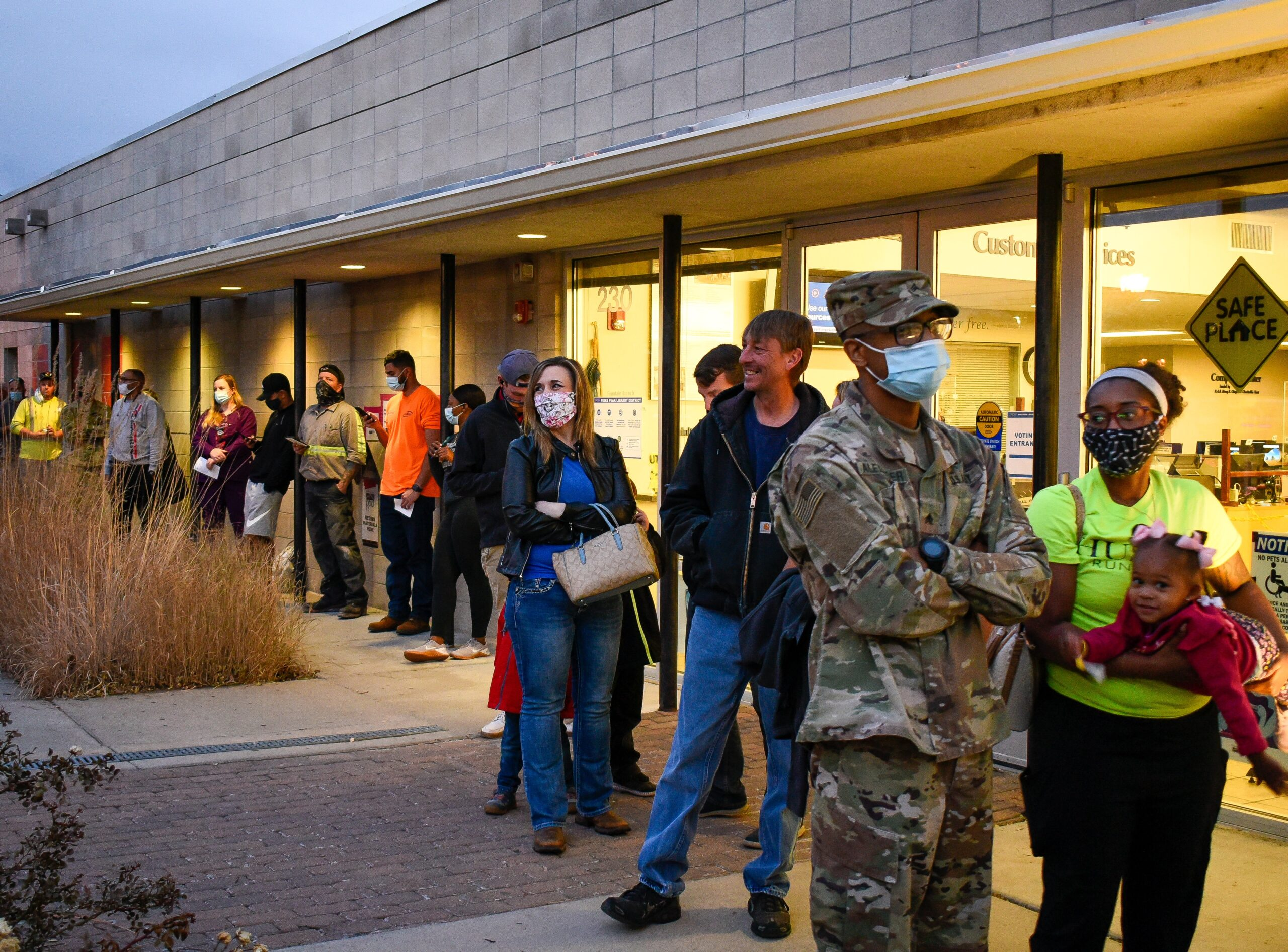 Army Sergeant Trey Alexander, his wife Jasmine and daughter Aria, 2, wait in line at the Fountain Library in Fountain, Colo. along with several others to vote in the 2020 election. A line wrapped around the building and some voters waited patiently from 30 minutes to an hour and a half.