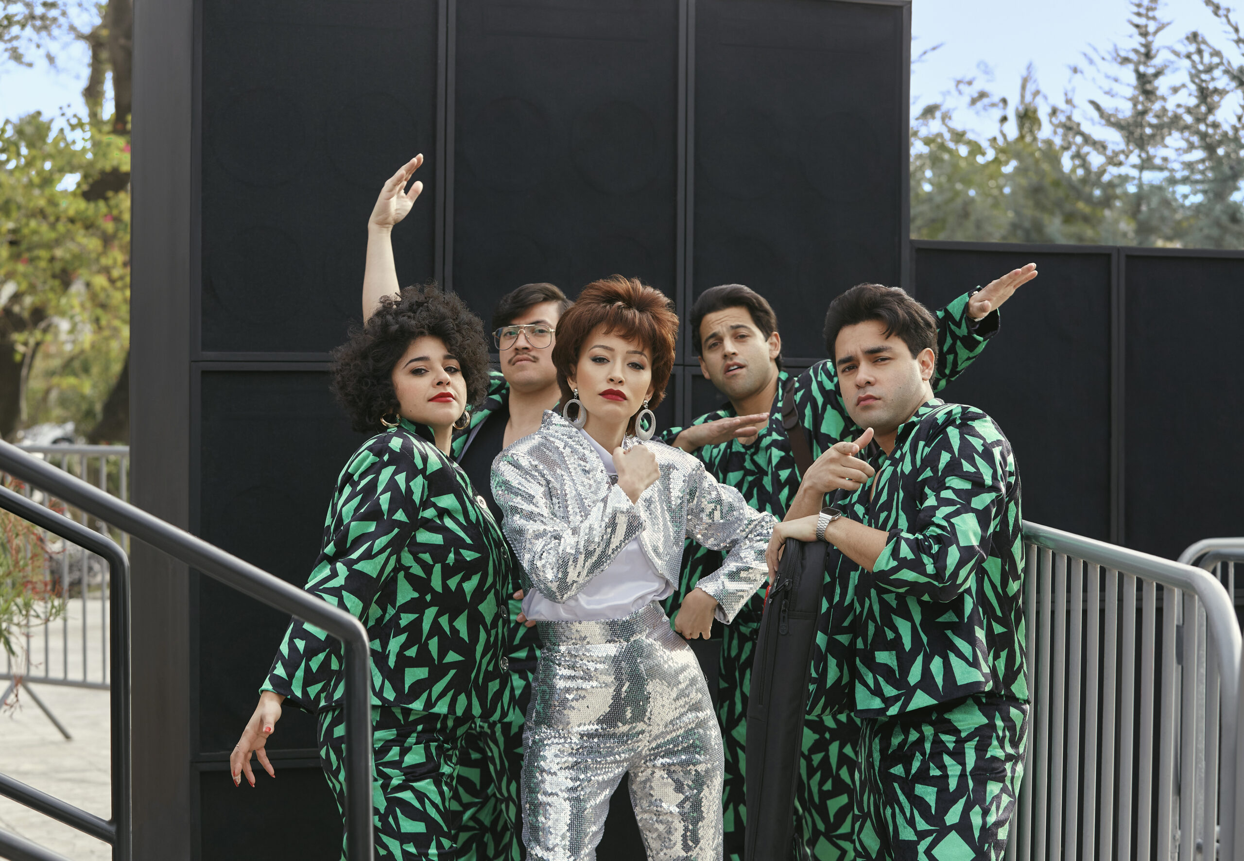 Selena The Series (L to R) Noemi Gonzalez as Suzette Quintanilla and Hunter Reese Pena as Ricky Vela and Christian Serratos as Selena Quintanilla and Paul Rodriguez, Jr. as Roger Garcia and Gabriel Chavarria as A.B. Quintanilla in episode 103.