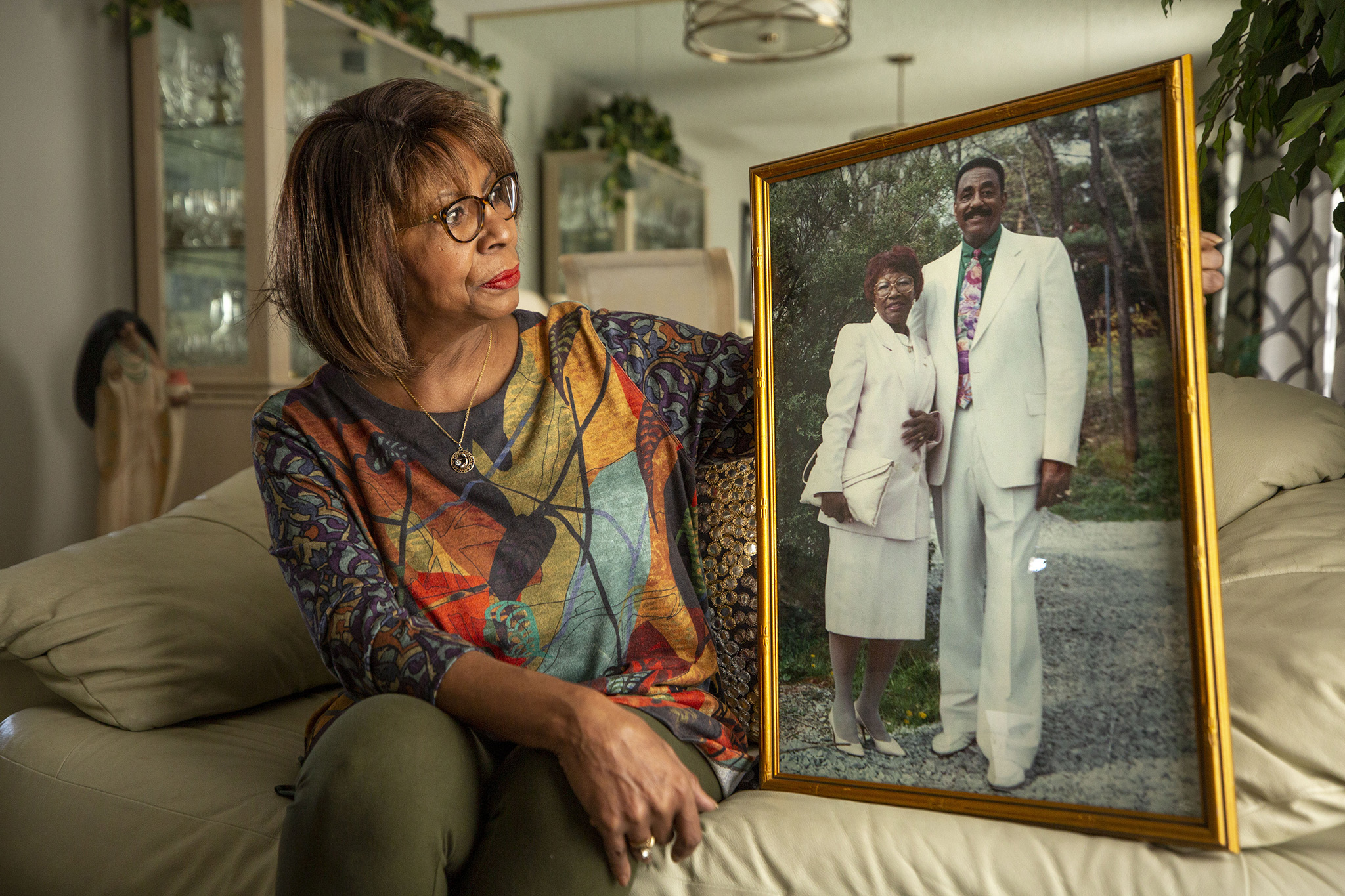 Jeannie Davis sits with a portrait of her parents, Dottie and James, inside her home in Aurora. Feb. 26, 2021.