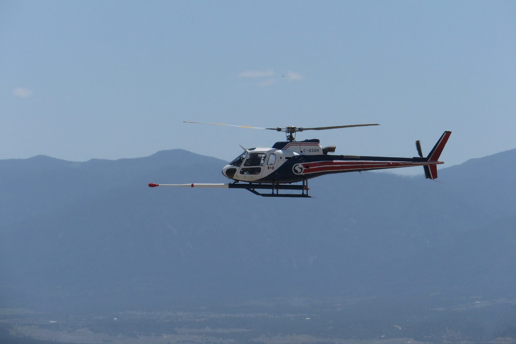 A low-flying helicopter surveys an area near the Wet Mountains.