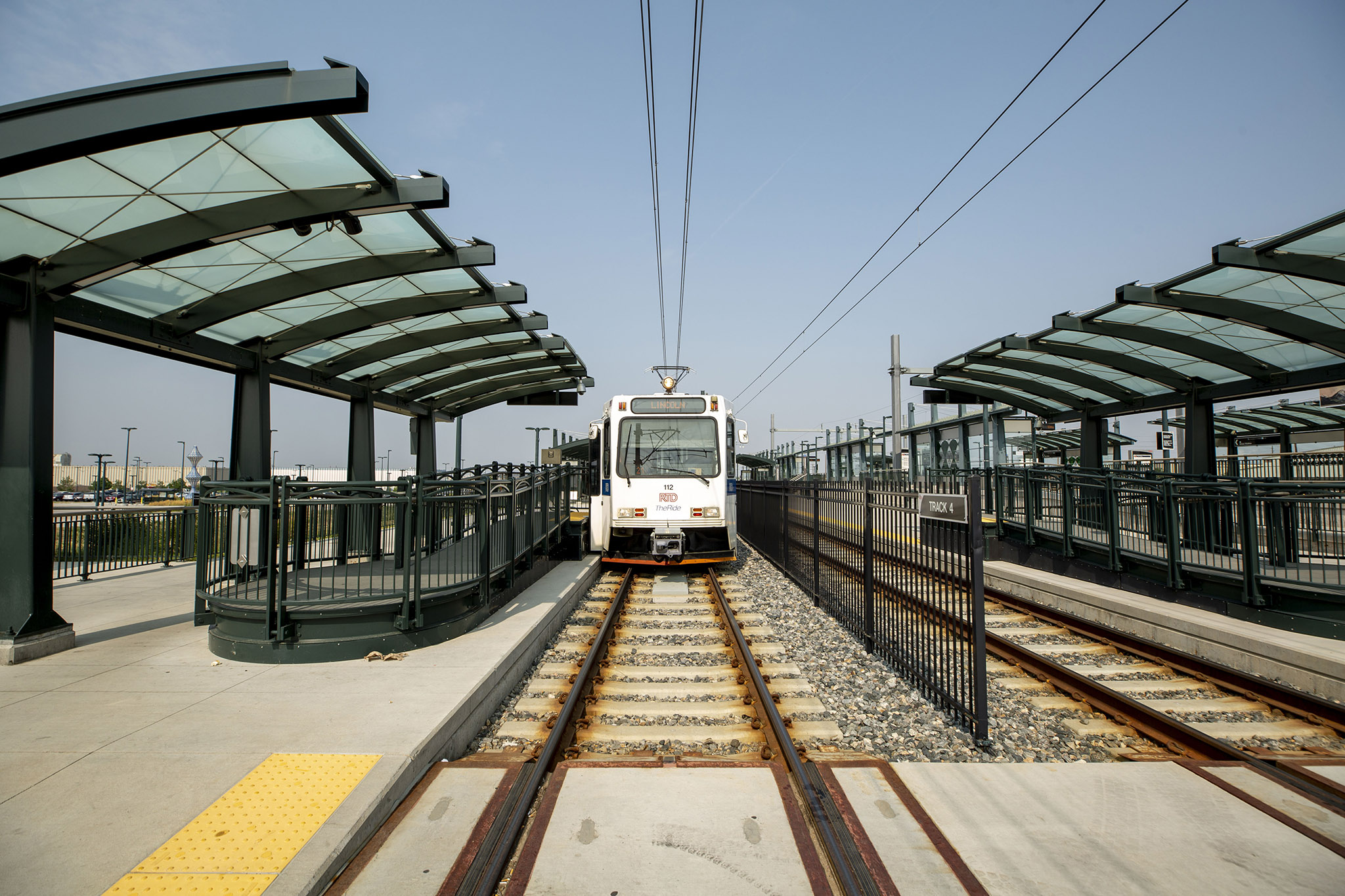 A light rail train waits for passengers at RTD's Peoria Street station in Aurora. Aug. 10, 2021.