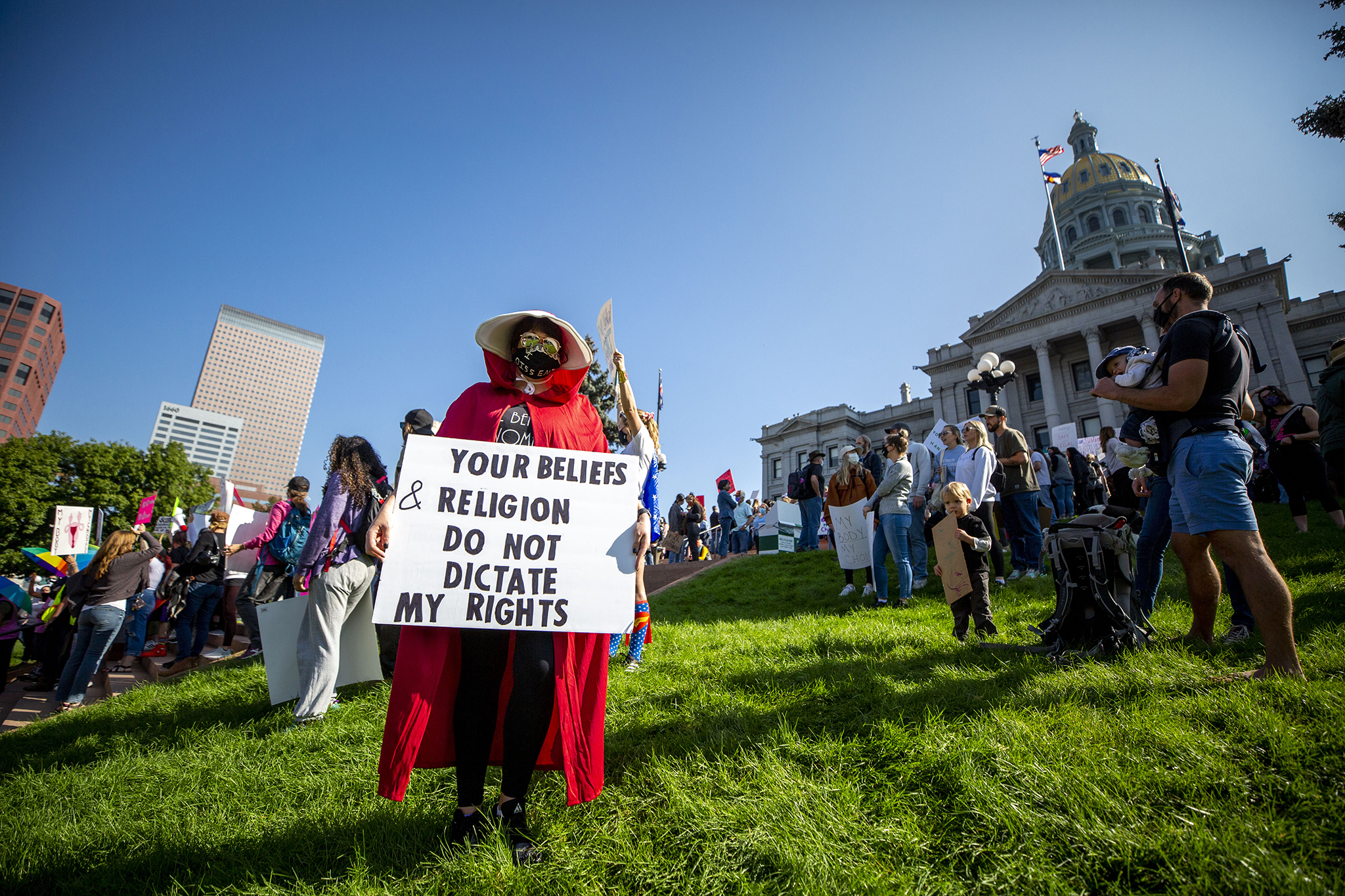 Lyndsay Ammon holds a protest sign during a rally for women's reproductive rights at the Colorado State Captiol. Oct. 2, 2021.