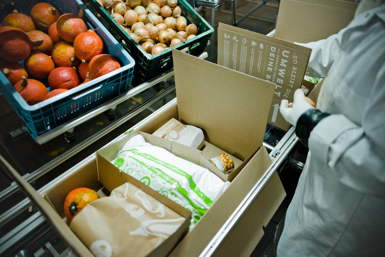 A worker packs a HelloFresh meal kit.