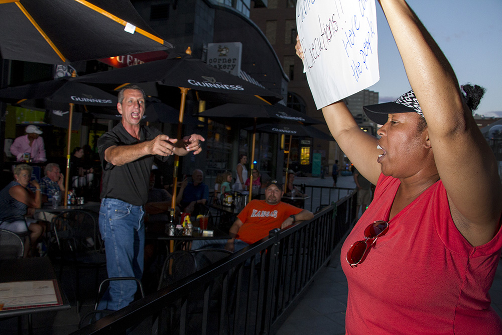 "Terry Berry (left) yells, ""Get a real job,"" in response to protesters like Patricia Williams who have flooded the 16th street mall on July 7 in response to high-profile killings of black men by police in recent days. (Kevin J. Beaty/Denverite)  black lives matter 5280; protest; march; denver; colorado; kevinjbeaty; denverite;"