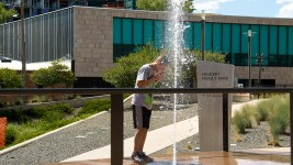 A boy stands in a fountain outside of the Denver Art Museum to escape the heat. (Chloe Aiello/Denverite)