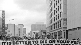 """'Mexican Americans, members of the Crusade for Justice (La Crusada Para Justicia) march in protest down 15th (Fifteenth) street in Denver, Colorado. They carry a large banner written in both English and Spanish, which reads: """"It Is Better to Die On Your Feet Than to Keep On Living On Your Knees"""" """"Es Mejor Morir de Pie, Que Seguir Viviendo de Rodillas.""""'  Between 1966 and 1970. (Shannon Garcia/Denver Public Library/Western History Collection/AUR-2152)   corky gonzales; crusade for justice; protest; historic; archival; archive; denver public library; dpl; denverite; denver post"""