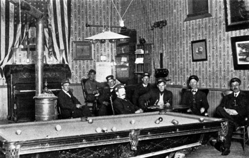 View of Denver Tramway Company conductors in uniform at the North Side Club in Denver, Colorado. Interior shows: pool table, piano, American flag, and a heater. November 1911. (Denver Public Library/Western History Collection/X-18384)  denver public library; dpl; archival; archive; historic; denver; colorado; denverite