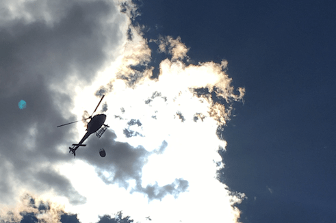 A helicopter flies near the Cold Springs Fire. (Andy Kenney/Denverite)