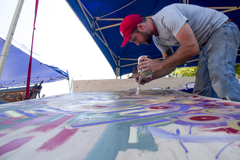 C2 Gallery owner Chad Copeland paints at the second annual West Colfax Mural Fest (Kevin J. Beaty/Denverite)  40 west arts district; west colfax; lakewood; kevinjbeaty; denver; denverite; art; craft; fair; colorado