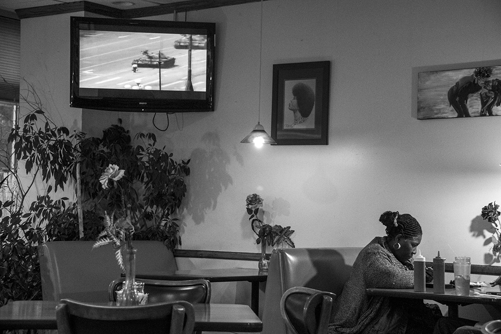 A famous symbol of resistance is seen on a TV screen in the  Welton Street Cafe, Five Points. (Kevin J. Beaty/Denverite)  welton street; five points; development; kevinjbeaty; denver; denverite; colorado;