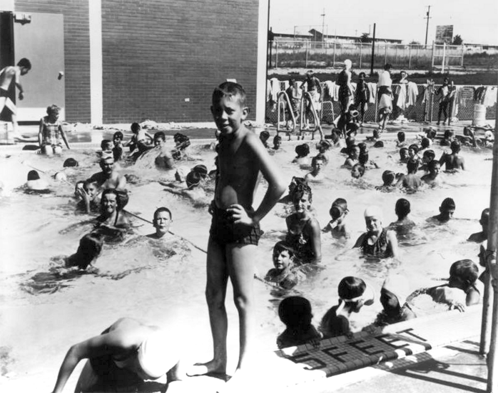 "Boys and girls play at this YMCA swimming pool in Littleton, Colorado. Some wear face masks; letters in the tile siding read: ""5 feet."" A brick wall, chain link fence, and YMCA club buildings are in the background. Circa 1961. (Lloyd Rule/Denver Public Library/Western History Collection/X-12074)