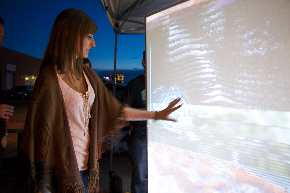 Woman touches the Alt Ethos cube prototype at Signal-to-Noise in RiNo. (Chloe Aiello/Denverite)