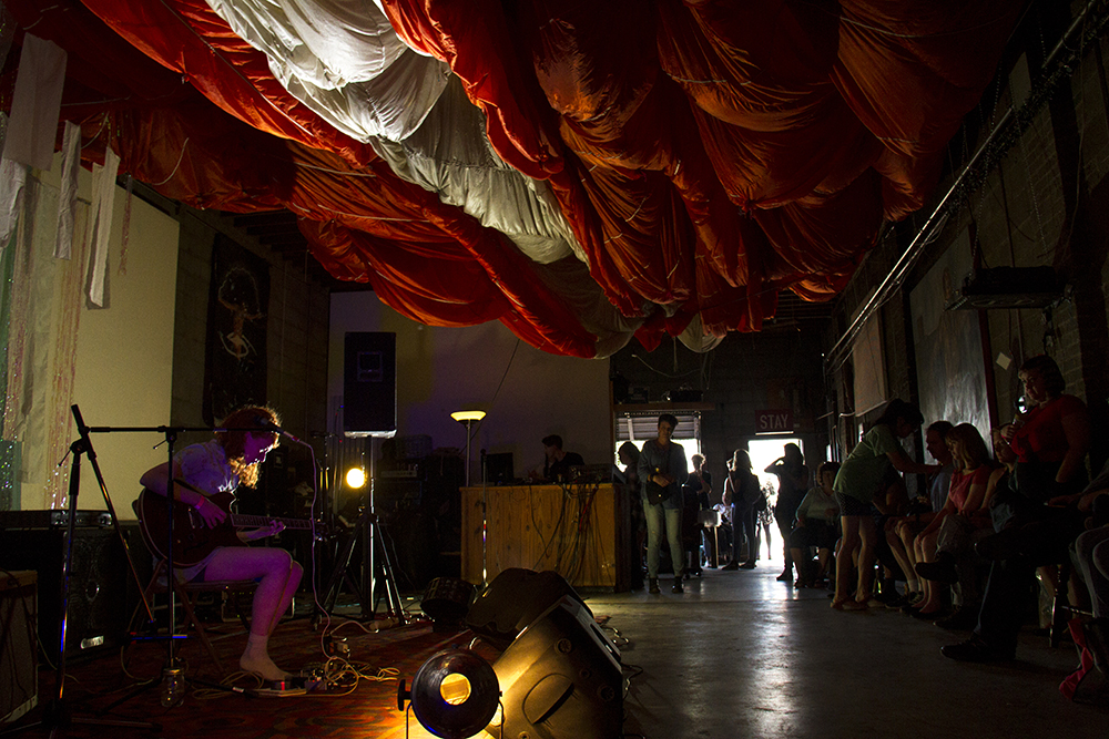 Experimental musician Cecilia McKinnon, AKA Star Canyon, plays to a growing crowd under a plush set. (Kevin J. Beaty/Denverite)