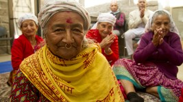 Monmay Baniya sits in a cirle of singing ladies during the Hindu Durga Puja celebration, held in Aurora's Lowry Park pavilion by the local community of Bhutanese/Nepali refugees. (Kevin J. Beaty/Denverite)