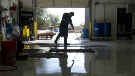 Workers clean rugs on a saturated floor at the Robert Mann Oriental Rugs building.(Kevin J. Beaty/Denverite)  oriental rugs; textile; robert mann; commercial real estate; business; stock show; development; kevinjbeaty; denverite; denver; colorado