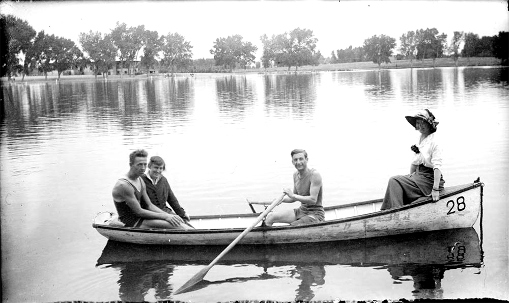 Outdoor portrait of men and women in a canoe at City Park Lake in Denver, Colorado; costume includes swimming suits and a flowered hat. Between 1904 and 1915. (Charles Lillybridge/History Colorado/90.152.417 DPLY)  history colorado; historic; denver public library; dpl; archive; archival; denverite