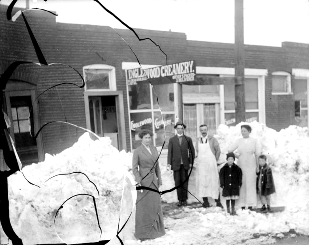 "Men, women, and children pose outdoors near a dairy store in Denver, Colorado. A sign on the building reads: ""Englewood Creamery Orders Placed"". Between 1904 and 1915. (Charles Lillybridge/History Colorado/90.152.906 DPLY)  history colorado; historic; denver public library; dpl; archive; archival; denverite"