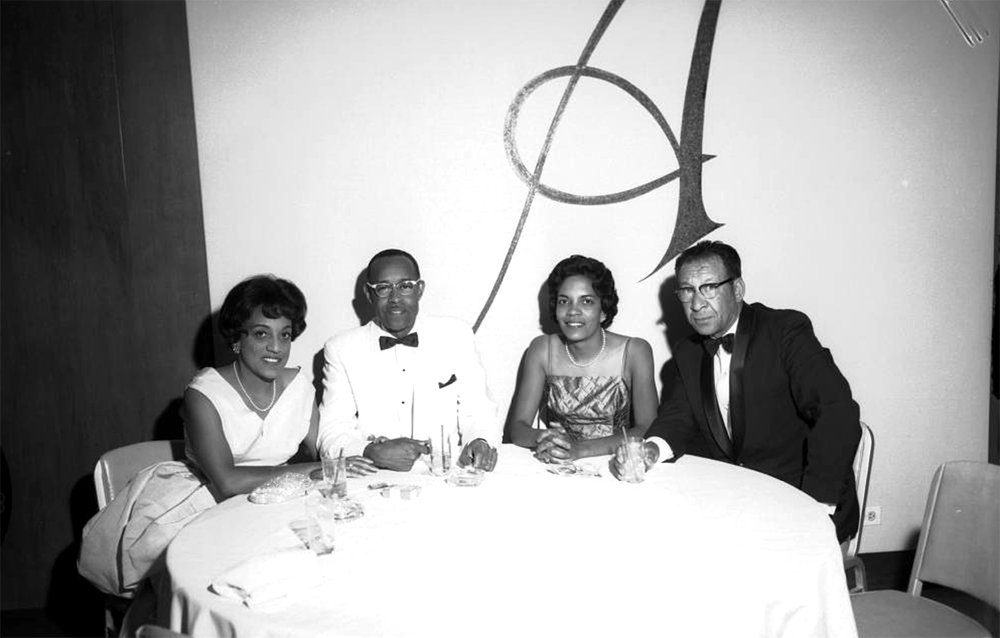 """Two African American couples, members of the La Lampions Club, sit at a table in a dance hall in Denver, Colorado. The men wear tuxedos, and the women wear party dresses. Drinks and cigarettes are on the table. A large script """"A"""" is painted on the wall in the distance. Between 1950 and 1960. (Burnis McCloud/Denver Public Library/Western History Collection/https://digital.denverlibrary.org/cdm/singleitem/collection/p15330coll22/id/59520/rec/6)  five points; historic; denver public library; dpl; archive; archival; denverite"""