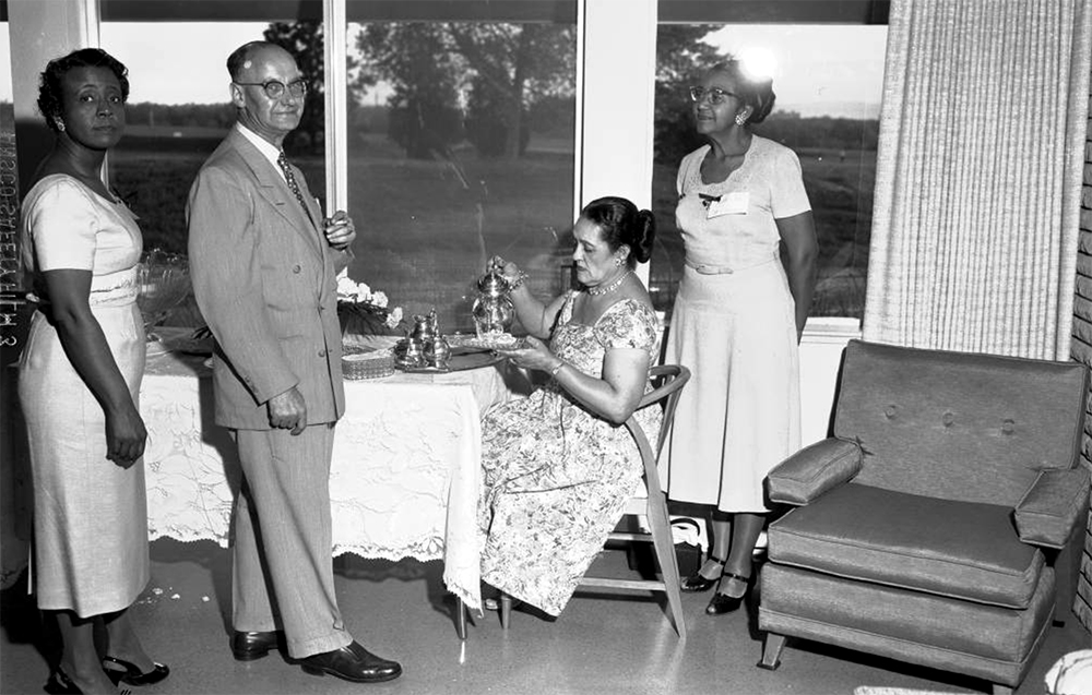View of a Links Club function. African American men and women gather for tea in the living room of a house in Denver, Colorado. A seated woman serves tea from a silver service. Between 1940 and 1950. (Burnis McCloud/Denver Public Library/Western History Collection/MCD-189)  five points; historic; denver public library; dpl; archive; archival; denverite