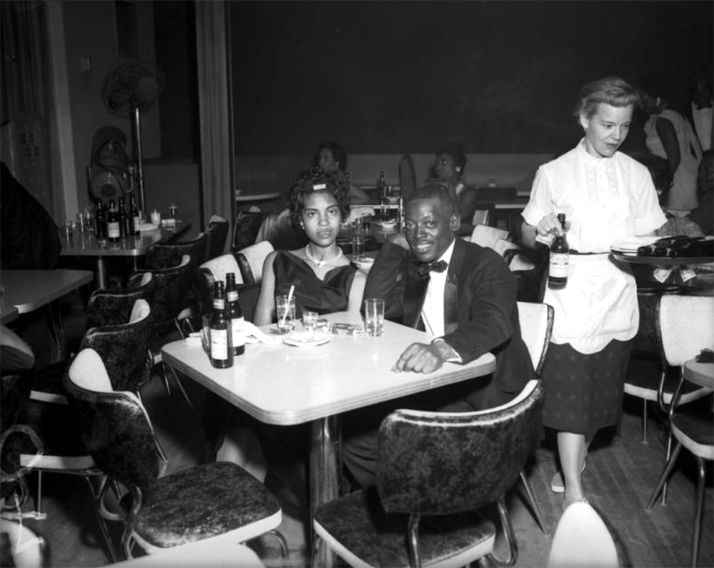 View of a Gay Dutchess club (The Gay Dutchess) function. An African American couple sit at a table in a bar of club in Denver, Colorado. The woman wears a party dress and the man wears a tuxedo. Cigarettes and beer bottles are on the table. A white waitress carries a tray and beer bottles near the table. Between 1950 and 1960. (Burnis McCloud/Denver Public Library/Western History Collection/MCD-151)  five points; historic; denver public library; dpl; archive; archival; denverite