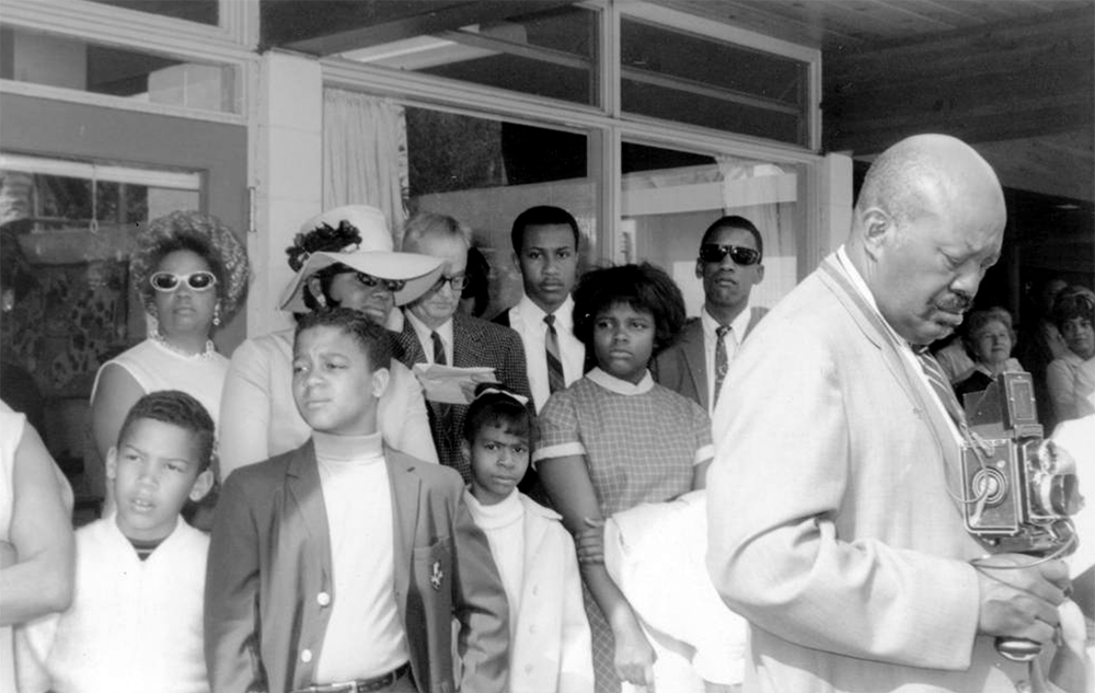 Men, women, and children stand near a building during the George Washington Carver Day Nursery dedication at 2260 Humboldt Street in the City Park West neighborhood of Denver, Colorado. Burnis McCloud stands by a camera near the group. 1966. (Clarence F. Holmes/Denver Public Library/Western History Collection/X-22345)  five points; historic; denver public library; dpl; archive; archival; denverite
