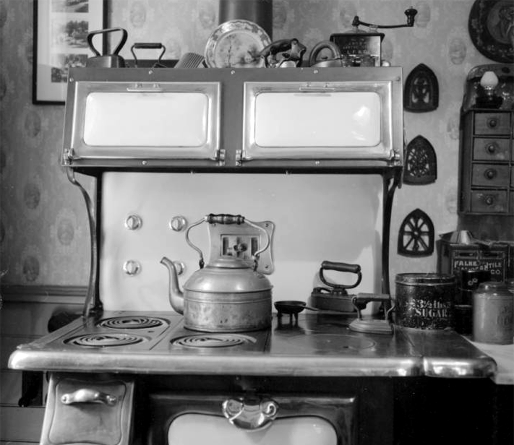 A stove and its stovepipe are in front of a wall with patterned wallpaper in a Central City residence. Between 1960 and 1980. (Sandra Dallas/Denver Public Library/Western History Collection/X-2886)  history colorado; historic; denver public library; dpl; archive; archival; denverite
