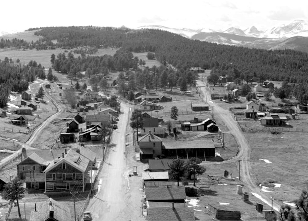 Houses stand along three main dirt roads in Gold Hill, a mining district about 12 miles northwest of Boulder in Boulder County, Colorado. Gold Hill was one of the first gold mining camps in Boulder County. By the 1950s, it was used mostly as a summer resort. The snow-capped peaks of the Continental Divide stand in the distance. Circa 1939. (Donald Kemp/Denver Public Library/Western History Collection/K-41)  five points; historic; denver public library; dpl; archive; archival; denverite