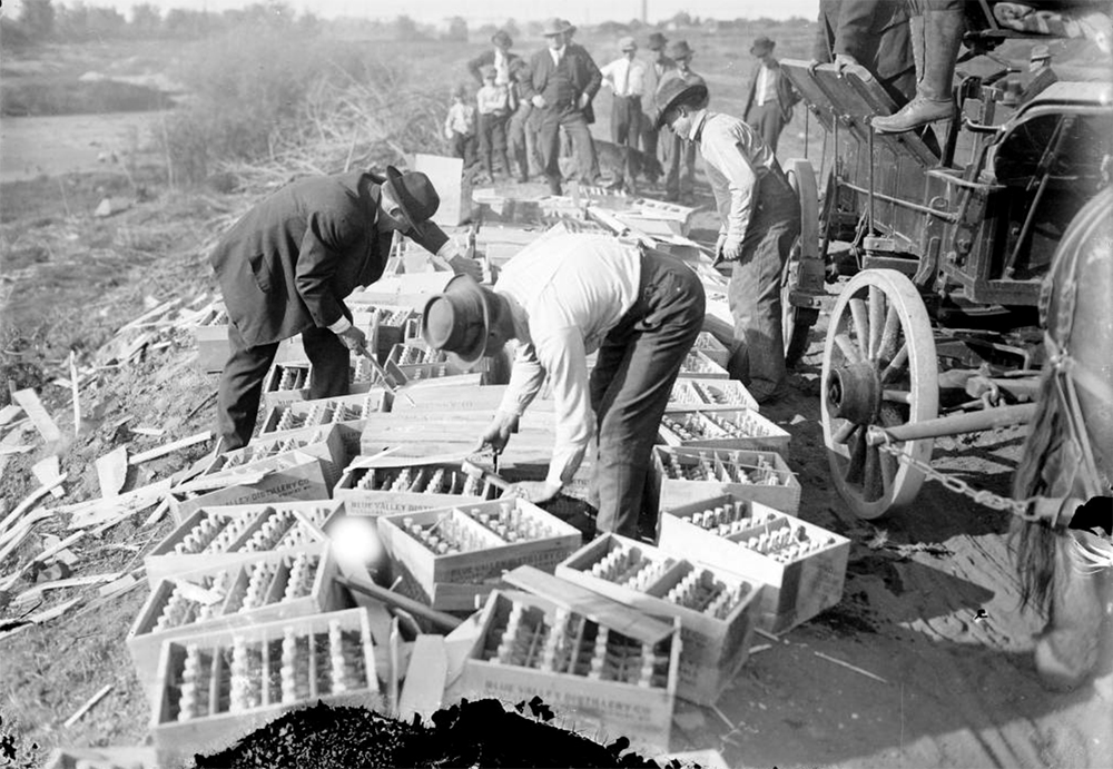 People watch men open cases of liquor from the Blue Valley Distillery Company during a Prohibition arrest in Colorado. The men use crowbars to open the wooden cases. Circa 1920. (Harry Mellon Rhoads/Denver Public Library/Western History Collection/Rh-1158)  historic; denver public library; dpl; archive; archival; denverite