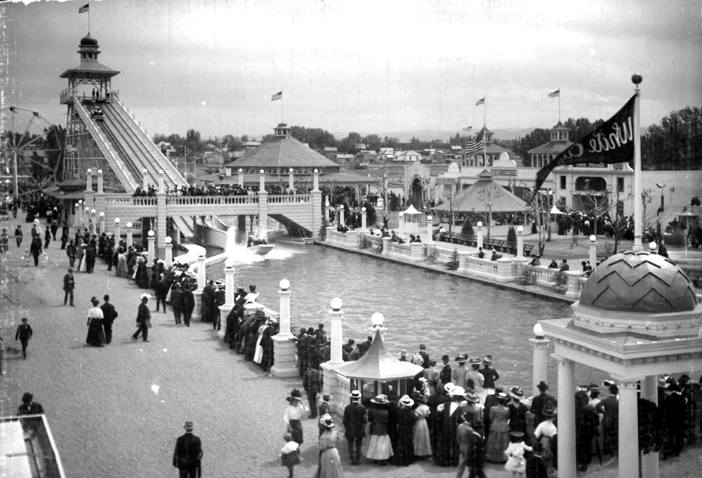 """View of ride called the Chutes (or the Big Splash), """"White City"""" (later called Lakeside Amusement Park), Lakeside, Colorado, near Denver; shows a large crowd of people gathered and watching water ride, edge of ferris wheel, other rides, a penny arcade, a large line by ticket gazebo, and wooden frame residences behind boundary of amusement park. Between 1908 and 1910. (Louis Charles McClure/Denver Public Library/Western History Collection/MCC-943)  historic; denver public library; dpl; archive; archival; denverite"""