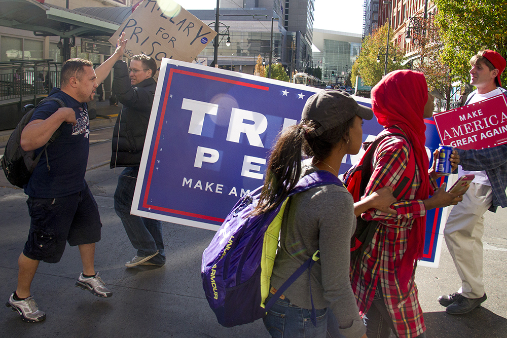 Jonathon Leddy (left) and Matt Callaway carry an enormous Trump/Pence sign down the 16th Street Mall. A passerby gives Leddy a high five. (Kevin J. Beaty/Denverite)  campaign; election; voting; vote; cbd; central business district; kevinjbeaty; denver; denverite; colorado; copolitics;