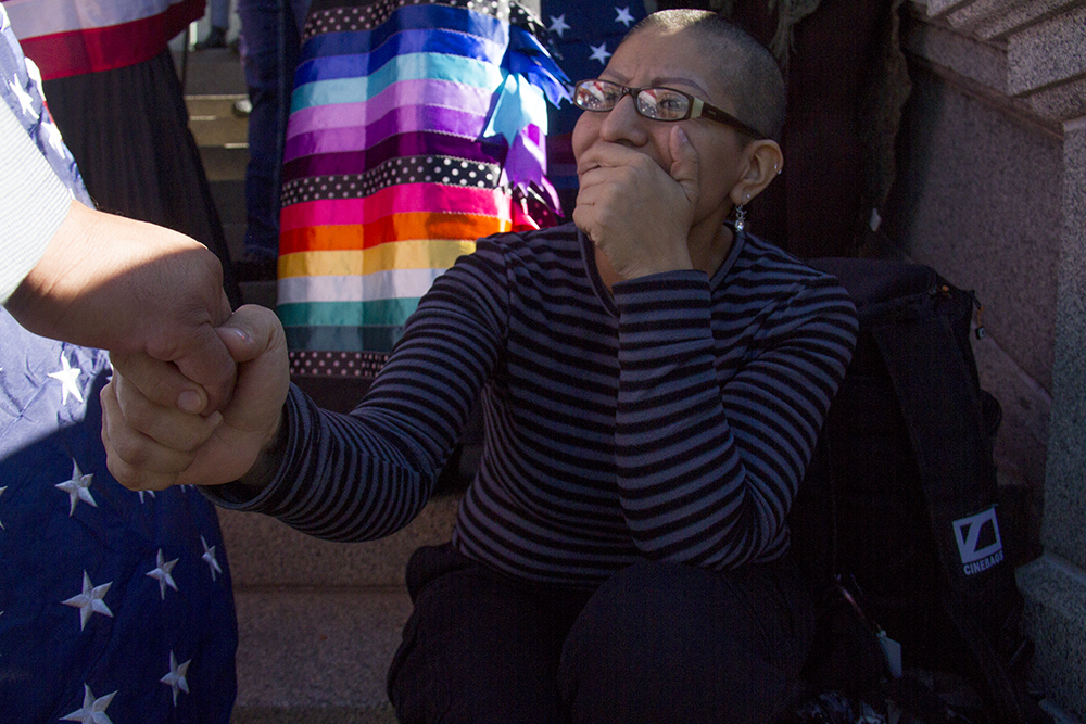 Colorado Immigrants Rights Coalition Campaign Coordinator Ezzie Dominguez shakes state representative Joe Salazar's hand on the Capitol steps during a rally against Donald Trump in reaction to his election just days prior. Nov. 10, 2016. (Kevin J. Beaty/Denverite)  rally; protest; trump; politics; copolitics; capitol; denver; denverite; colorado; kevinjbeaty; election;