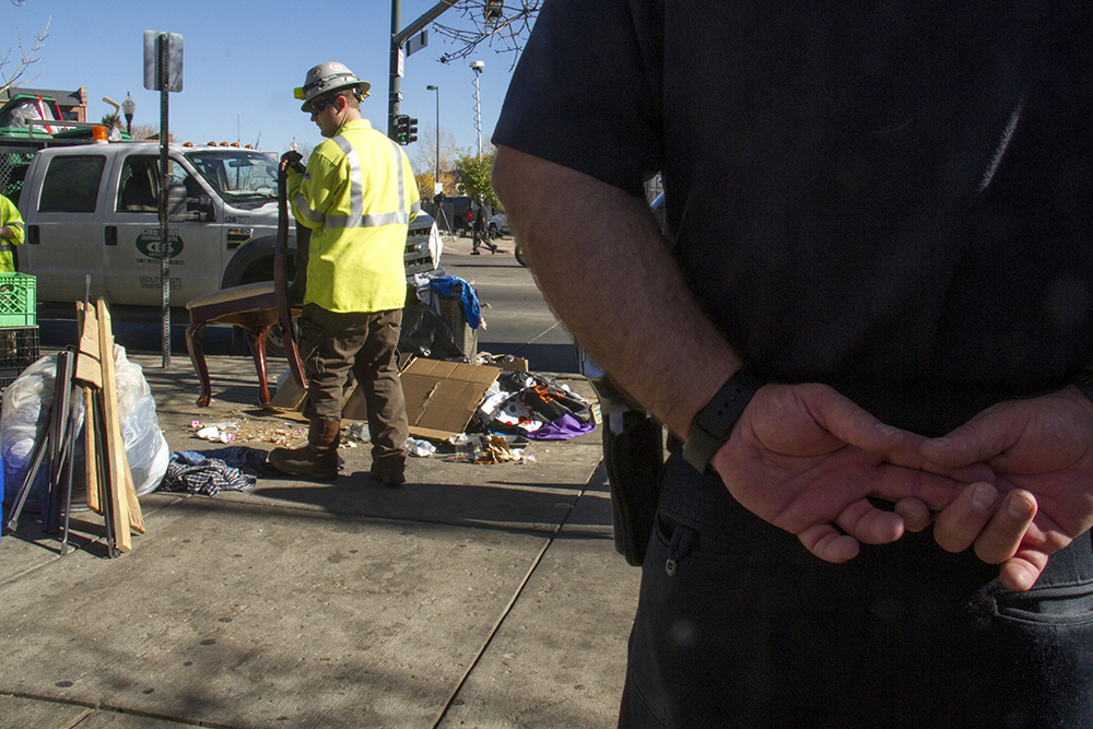 """City workers sort garbage from personal items, loading the former into a garbage truck and the latter into garbage bins for 30-day storage. """"Homeless sweeps"""" on Nov. 15, 2016. (Kevin J. Beaty/Denverite)homeless; sweeps; denver rescue mission; police; justice; kevinjbeaty; denver; denverite; colorado; camping ban; right to rest;"""
