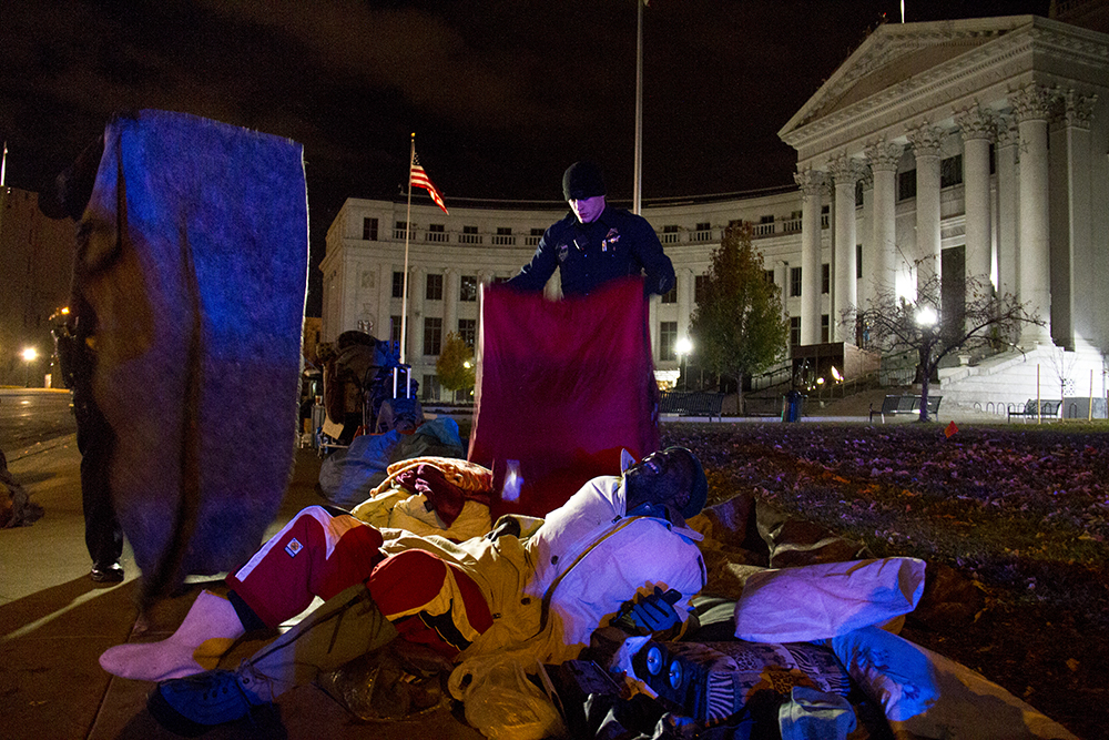 Police officers take away Jerry Burton's blankets, protocol for urban camping ban violators who refuse to leave after warnings. Protesters who have set up camp in front of the City and County Building to denounce Denver's urban camping ban are removed by police. Nov. 29, 2016. (Kevin J. Beaty/Denverite)  camping ban; right to rest; homeless sweeps; city and county building; police; protest; kevinjbeaty; denver; denverite; colorado;
