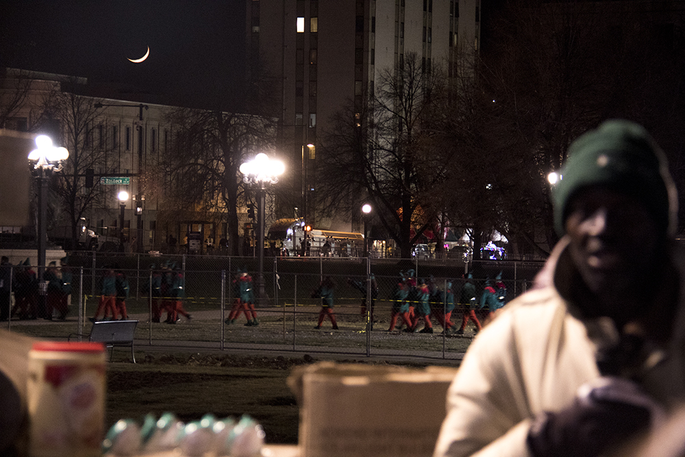 Jerry Burton speaks at a right to rest protest  as elves pass in the background during the parade of lights. Dec. 2, 2016. (Kevin J. Beaty/Denverite)  camping ban; protest; right to rest; homeless; parade of lights; holiday; christmas; civic center; kevinjbeaty; denver; denverite; colorado;