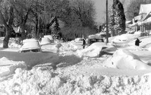 One man carries a shovel while two others shovel snow on a residential street after the snowstorm of 1982 in Denver, Colorado. (Denver Public Library/Western History Collection/X-29020)  archive; archival; historic; denver public library; dpl; western history collection; blizzard; snowstorm; weather; cowx; denverite; denver; colorado;
