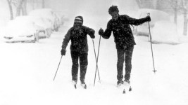 Two people ski down a Denver, Colorado street in the snowstorm of 1982. Shows cross country skis and poles. (Denver Public Library/Western History Collection/X-29021)  archive; archival; historic; denver public library; dpl; western history collection; blizzard; snowstorm; weather; cowx; denverite; denver; colorado;