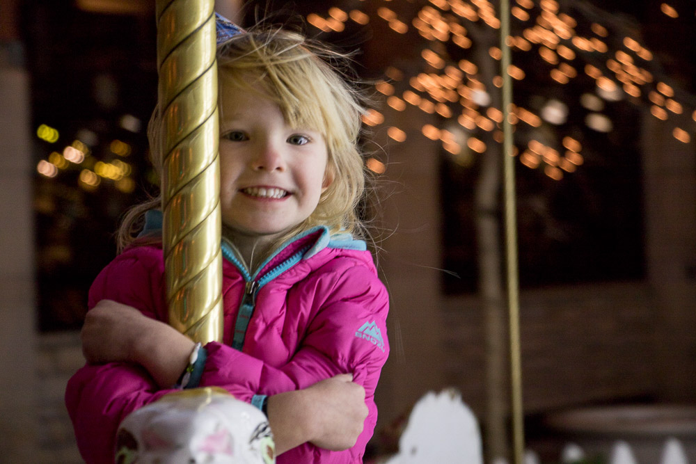 Eden Crosby at the Denver Pavilions holiday carousel. (Chloe Aiello/Denverite)