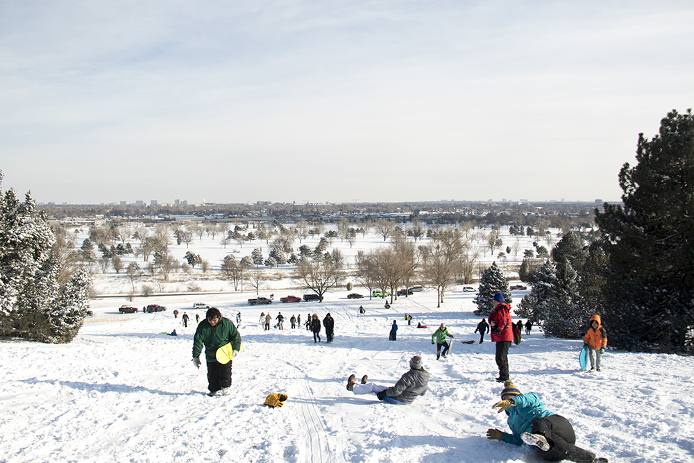 Young and old alike gather atop Ruby Hill to fly down it into the snow. Dec. 17, 2016. (Kevin J. Beaty/Denverite)  snow day; winter; sledding; denver; denverite; colorado; kevinjbeaty;