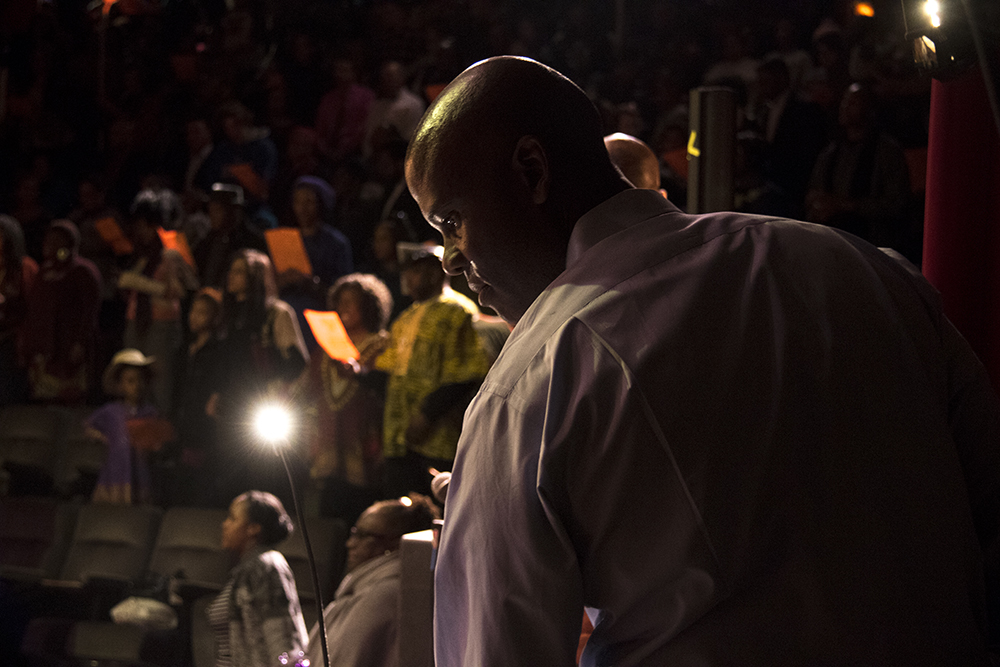"""""""Brother"""" Jeff Fard directs the show from stage right. The first night of Kwanzaa at the Cleo Parker Robinson Dance Theatre, Dec. 26, 2016. (Kevin J. Beaty/Denverite)kwanzaa; Cleo Parker Robinson Dance Theatre; holidays; denver; denverite; kevinjbeaty; colorado; five points;"""